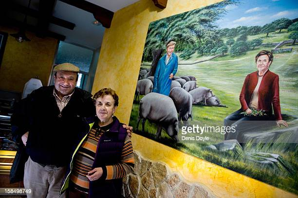 Faustino Prieto owner of the small familyrun Iberian ham business is photographed with his wife Candy Guerrero Jimenez beside a mural of themselves...