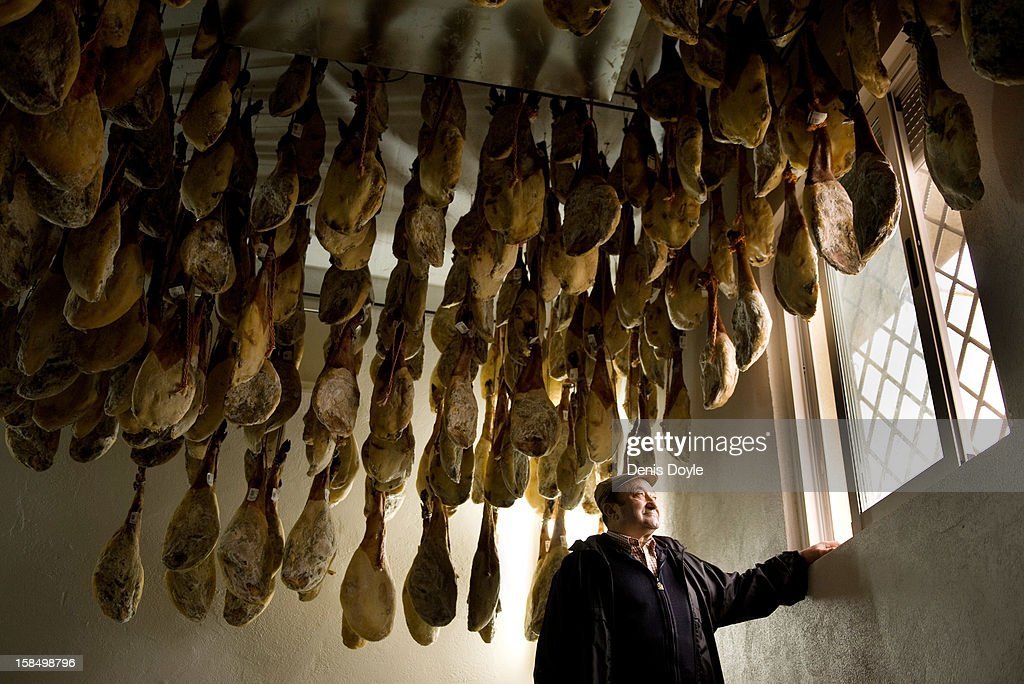Faustino Prieto, owner of the small family-run Iberian ham business looks out the window beside legs of dry-cured Jamon Iberico de bellota in the village of Cespedosa on December 14, 2012 near Salamanca, Spain. Dry-cured Iberian ham or Jamon Iberico is a favourite amongst Spaniards and producers are hoping for improved sales over the busy christmas period. The jamon legs are usually dry-cured for up to three years after the pigs have been few on a diet of acorns in the last three months of their lives.
