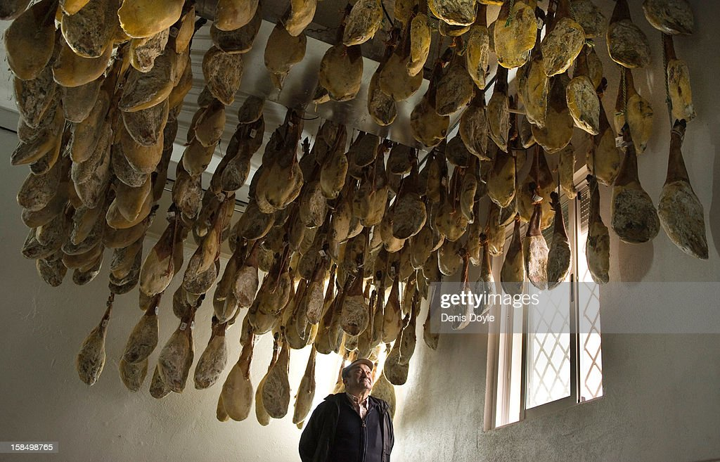 Faustino Prieto, owner of the small family-run Iberian ham business, looks up at legs of dry-cured Jamon Iberico de bellota in the village of Cespedosa on December 14, 2012 near Salamanca, Spain. Dry-cured Iberian ham or Jamon Iberico is a favourite amongst Spaniards and producers are hoping for improved sales over the busy christmas period. The jamon legs are usually dry-cured for up to three years after the pigs have been few on a diet of acorns in the last three months of their lives.