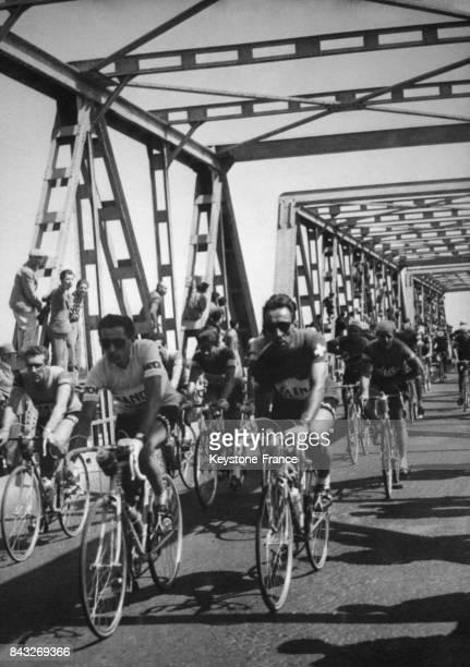 Fausto Coppi et le coureur suisse Emilio Croci Torti traversant un pont lors de la 16e étape du Giro en Italie le 10 juin 1955