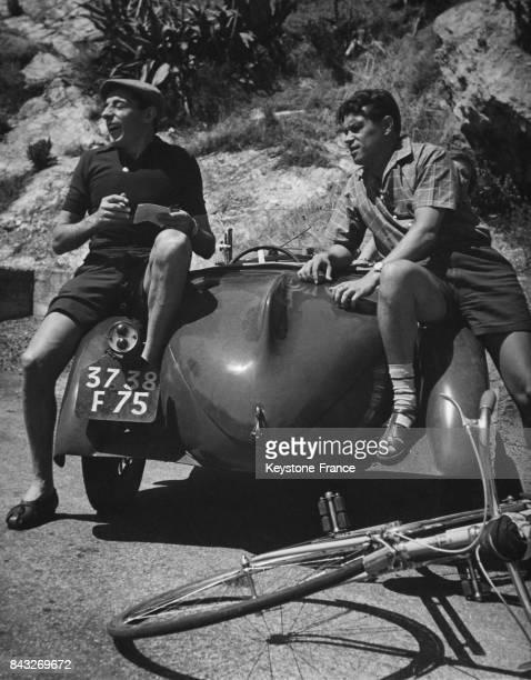 Fausto Coppi riant assis sur une voiture au bord d'une route en Italie