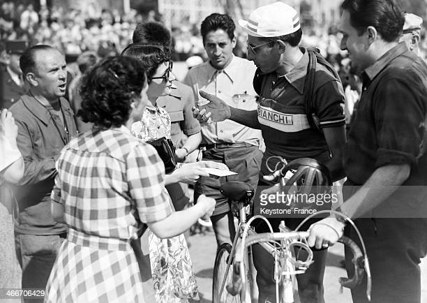 Fausto Coppi speaking with fans in front of the Invalides a few minutes before the start of a stage of the Tour de France 1951 in July 1951 in Paris...