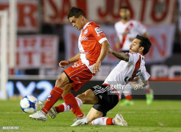 Fausto Montero of Argentinos Juniors fights for the ball with Ignacio Scocco of River Plate during a match between River Plate and Argentinos Juniors...