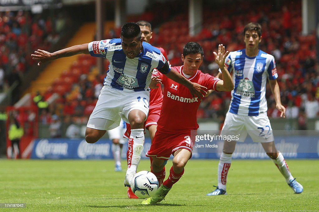 Fausto Pinto (L) of Toluca struggles for the ball with Daniel Luduena (R) of Tijuana during the match between Toluca and Pachuca as part of the Apertura 2013 Liga Bancomer MX at Nemesio Diez Stadium on july 21, 2013 in Toluca, Mexico.