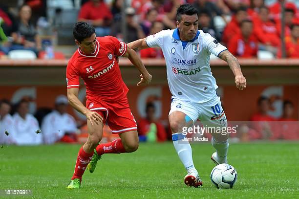 Fausto Pinto of Toluca struggles for the ball with Esteban Paredes of Queretaro during a match between Toluca and Queretaro as part of the Apertura...