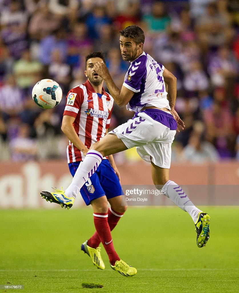 Fausto Rossi (R) of Real Valladolid CF battles for the ball with <a gi-track='captionPersonalityLinkClicked' href=/galleries/search?phrase=David+Villa&family=editorial&specificpeople=467566 ng-click='$event.stopPropagation()'>David Villa</a> of Club Atletico de Madrid during the La Liga match between Real Valladolid CF and Club Atletico de Madrid at Estadio Jose Zorilla on September 21, 2013 in Valladolid, Spain.