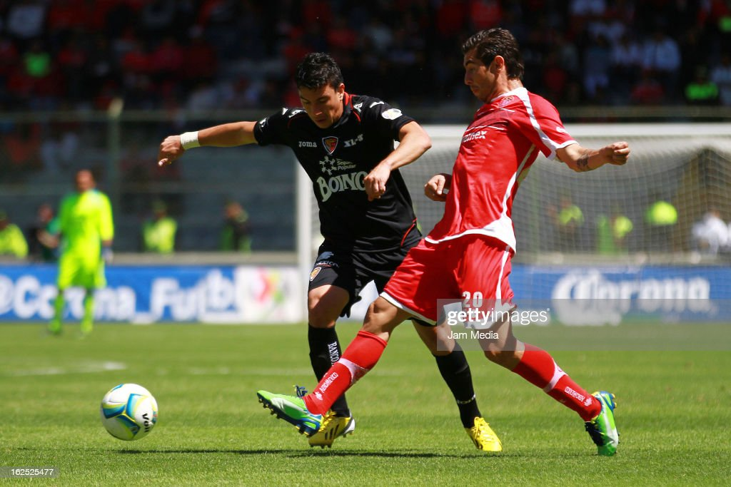 Favio Santos of Toluca struggles for the ball with Jorge Rodriguez of Jaguares during a match between Toluca and Jaguares as part of 2013 Clausura...