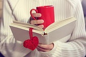 man wearing a white sweater love reading a book and drinking a hot drink