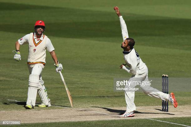Fawad Ahmed of Victoria bowls as Jake Lehmann watches during day three of the Sheffield Shield match between Victoria and South Australia at...