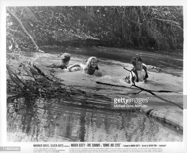 Faye Dunaway and Warren Beatty cross a river in a scene from the film 'Bonnie and Clyde' 1967