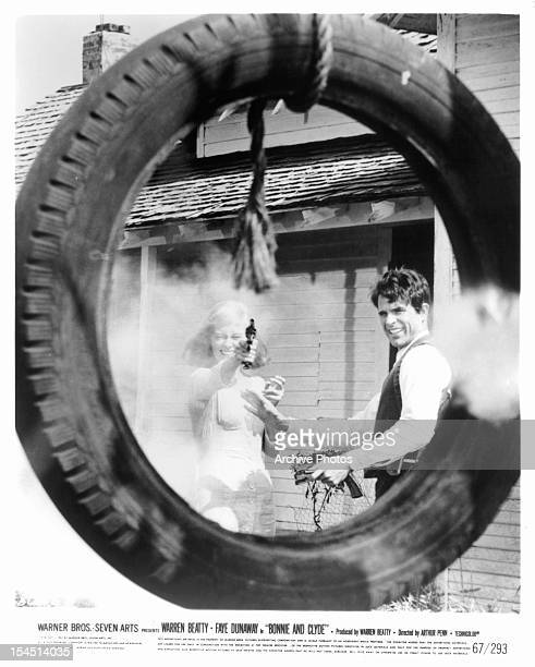 Faye Dunaway shoots through a tire as Warren Beatty watches in a scene from the film 'Bonnie And Clyde' 1967
