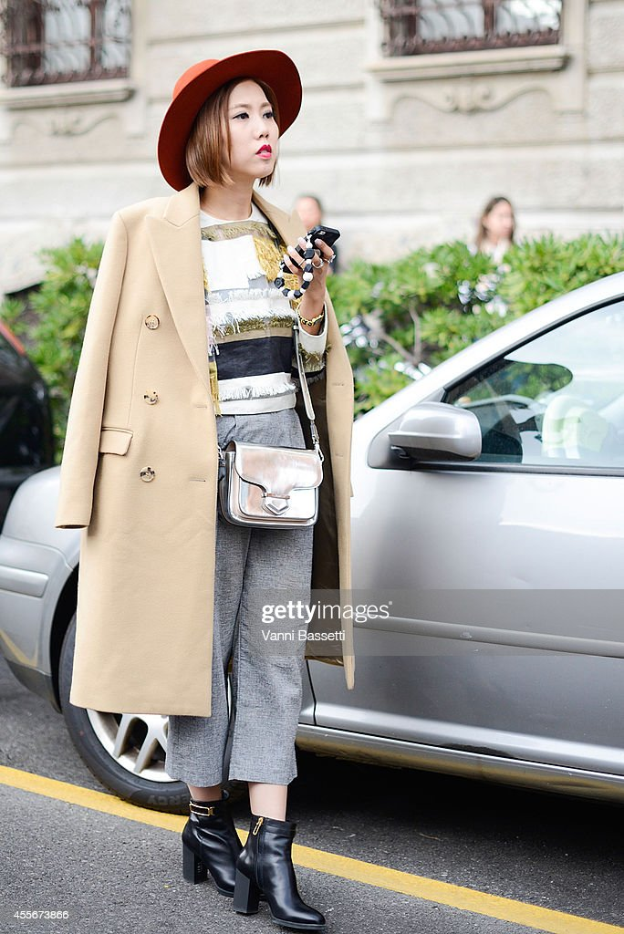 Faye Tsui wears a Michael Kors jacket Phillip Lim top Tod's bag and shoes on September 18 2014 in Milan Italy