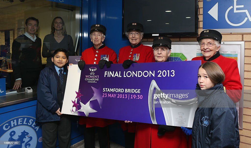 Faye White and Graeme le Saux (behind the window) pose with children and Chelsea Pensioners during the ticket launch for the UEFA Women's Champions League Final at Stamford Bridge on January 22, 2013 in London, England.