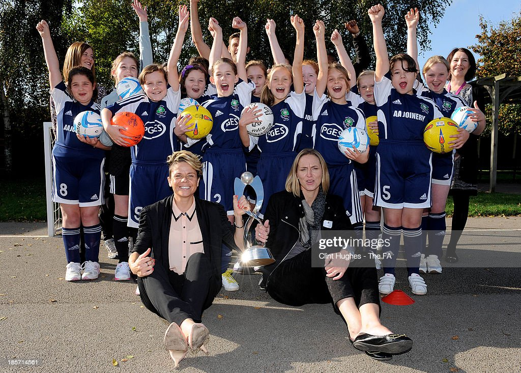 Faye White (R) and Sue Smith (L) pose with the European Women's Under 17 trophy andn school children during the UEFA European Women's Under 17 Championship Draw at Outwoods Primary School on October 24, 2013 in Burton upon Trent, England