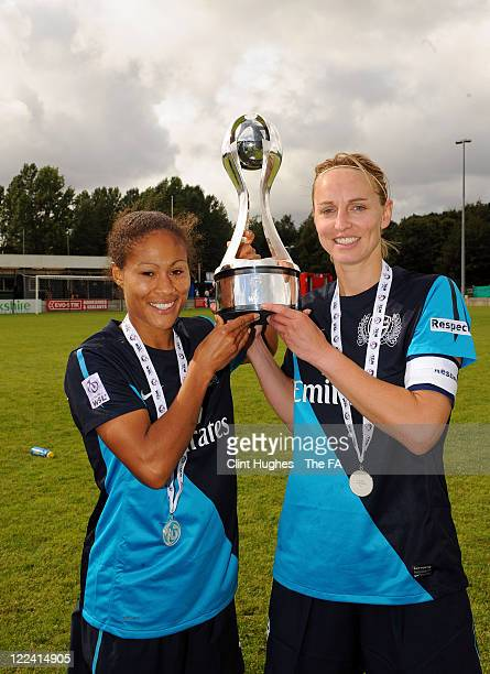 Faye White captain of Arsenal and her teammate Rachel Yankey celebrate with the WSL trophy during the FA WSL match between Liverpool Ladies FC and...