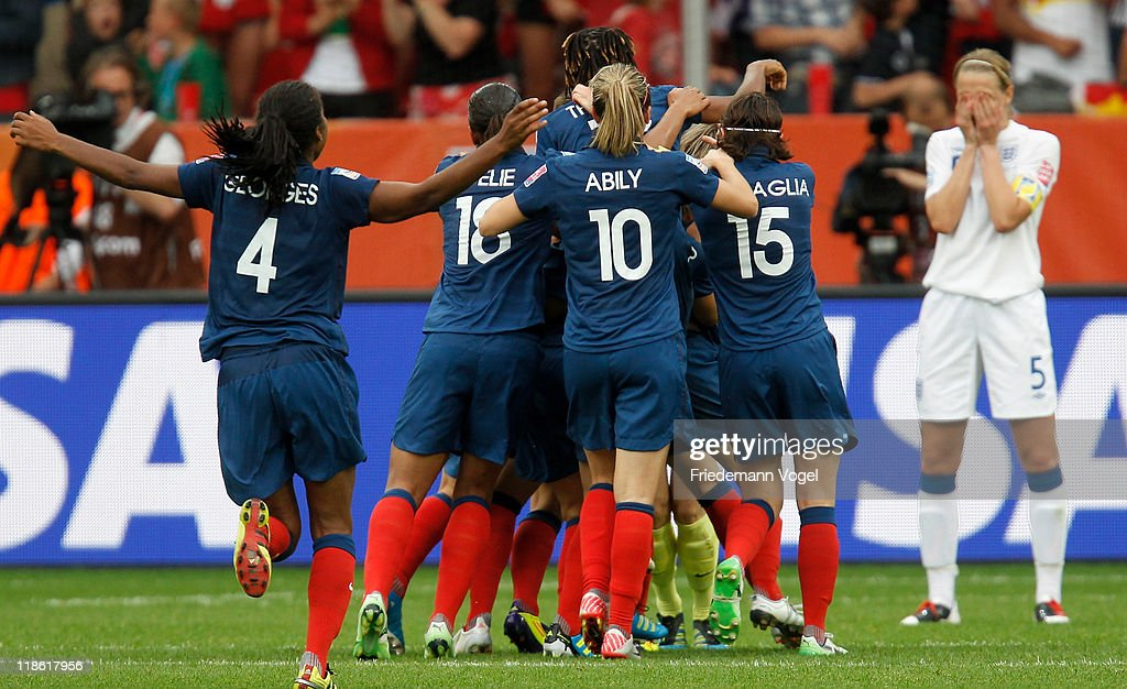Faye White (R) of England looks dejected after missing the decisive penalty as team of France celebrates after winning the FIFA Women's World Cup 2011 Quarter Final match between England and France at the FIFA Women's World Cup Stadium Leverkusen on July 9, 2011 in Leverkusen, Germany.