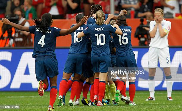 Faye White of England looks dejected after missing the decisive penalty as team of France celebrates after winning the FIFA Women's World Cup 2011...