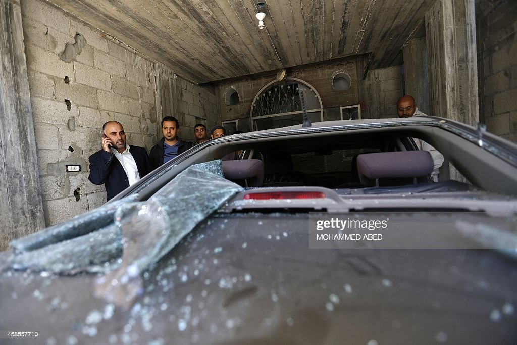 Fayez Abu Eitta a Fatah leader in Gaza speaks on the phone as he inspects the damage to his car in the parking lot of his home in Beit Lahya northern...