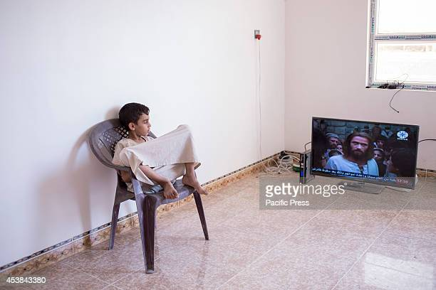 Fayezs son watches a TV movie about the life of Jesus Christ in the flat the family have been allocated Qaraqosh Iraq