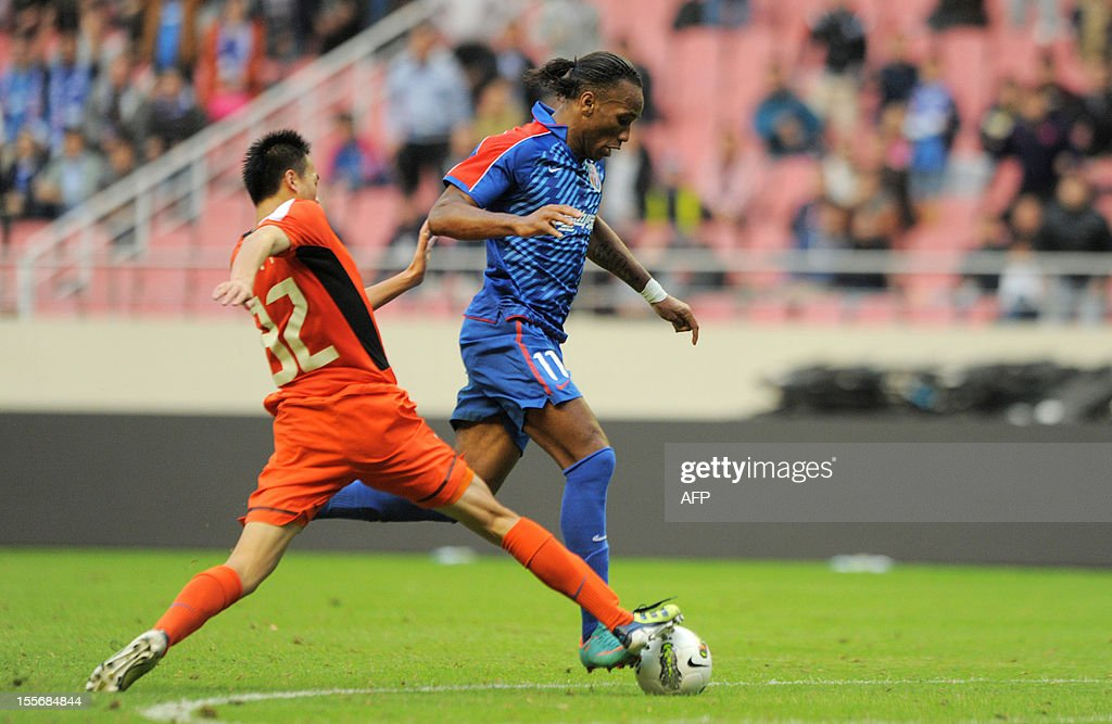 Fbl-Asia-CHN-Drogba,FOCUS BY CAMERON WILSON In this picture taken on November 3, 2012 former Chelsea star Didier Drogba (R) dribbles the ball for his team, Shanghai Shenhua, beating Qingdao 3-0 in the last game of the Chinese Super League (CSL) in Shanghai. Three coaches, boardroom upheaval and a reported players' strike -- Didier Drogba's first season in China hasn't exactly been smooth, but it looks like he'll stick around next year.