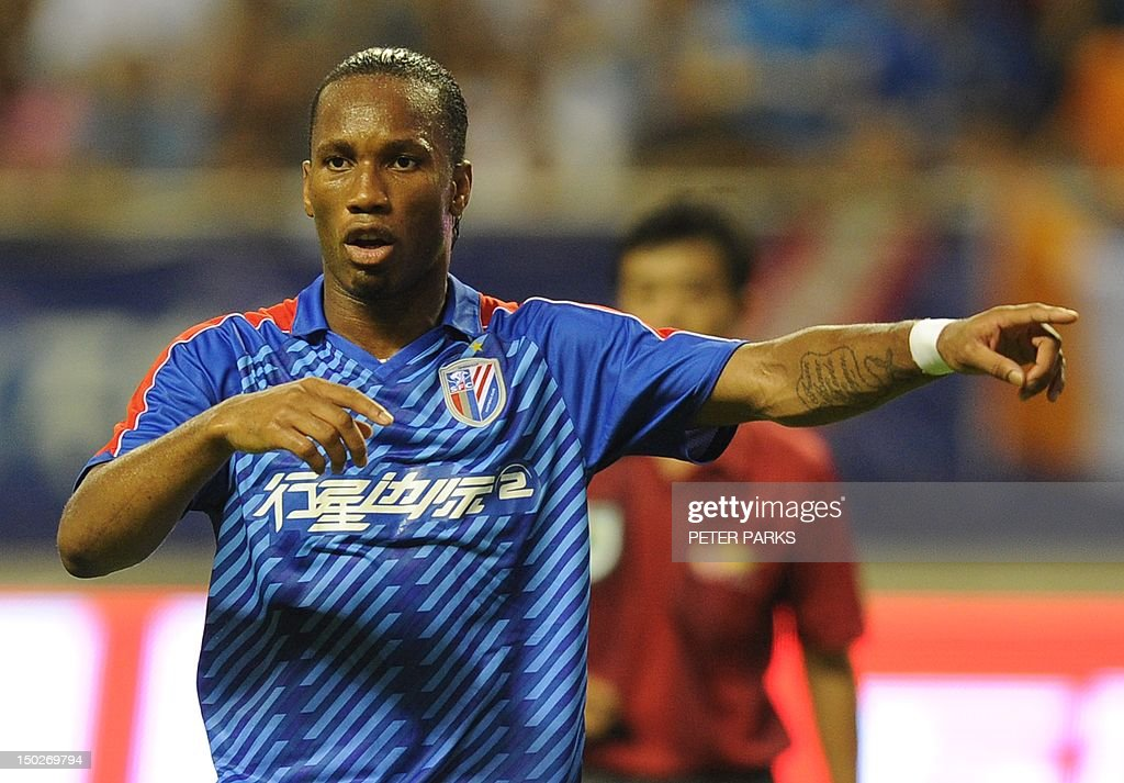 Fbl-Asia-CHN-Drogba,FOCUS by Cameron Wilson This photo taken on August 4, 2012 shows Didier Drogba gesturing as he plays for Shanghai Shenhua FC in their game against Hangzhou Greentown in Shanghai Hongkou Stadium. A month after arriving in China, Drogba is living up to the expectations of fans and players who have given him the new nickname 'Devil Beast' for his strength. AFP PHOTO/Peter PARKS