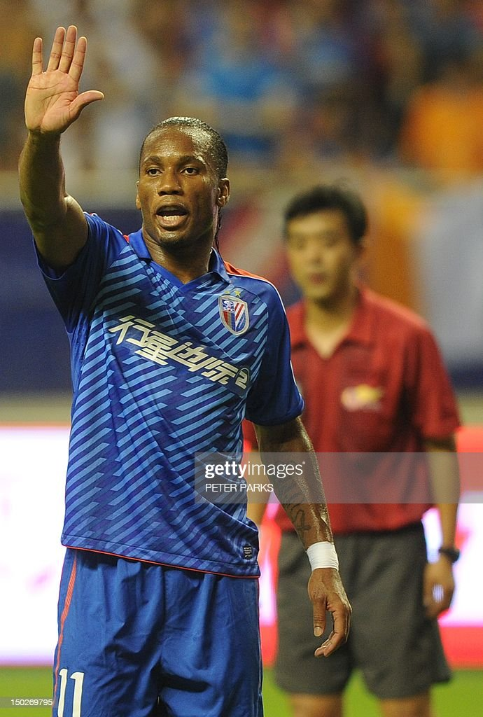 Fbl-Asia-CHN-Drogba,FOCUS by Cameron Wilson This photo taken on August 4, 2012 shows Didier Drogba (L) gesturing as he plays for Shanghai Shenhua FC in their game against Hangzhou Greentown in Shanghai Hongkou Stadium. A month after arriving in China, Drogba is living up to the expectations of fans and players who have given him the new nickname 'Devil Beast' for his strength. AFP PHOTO/Peter PARKS