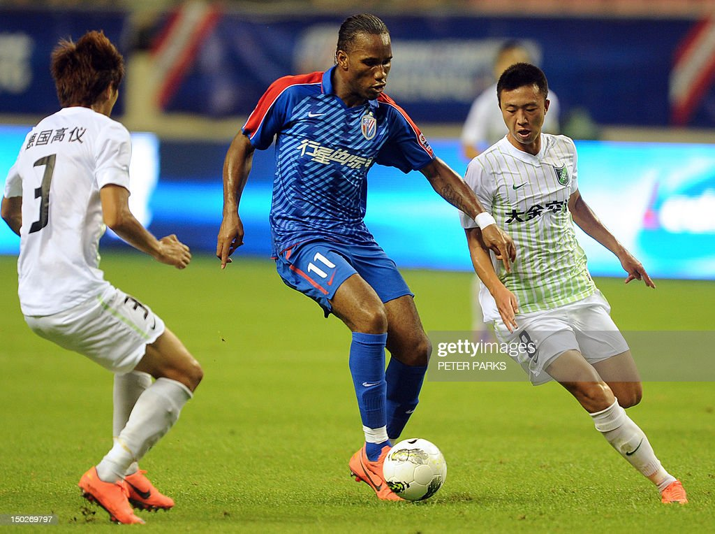Fbl-Asia-CHN-Drogba,FOCUS by Cameron Wilson This photo taken on August 4, 2012 shows Didier Drogba (C) playing for Shanghai Shenhua FC in their game against Hangzhou Greentown in Shanghai Hongkou Stadium. A month after arriving in China, Drogba is living up to the expectations of fans and players who have given him the new nickname 'Devil Beast' for his strength. AFP PHOTO/Peter PARKS