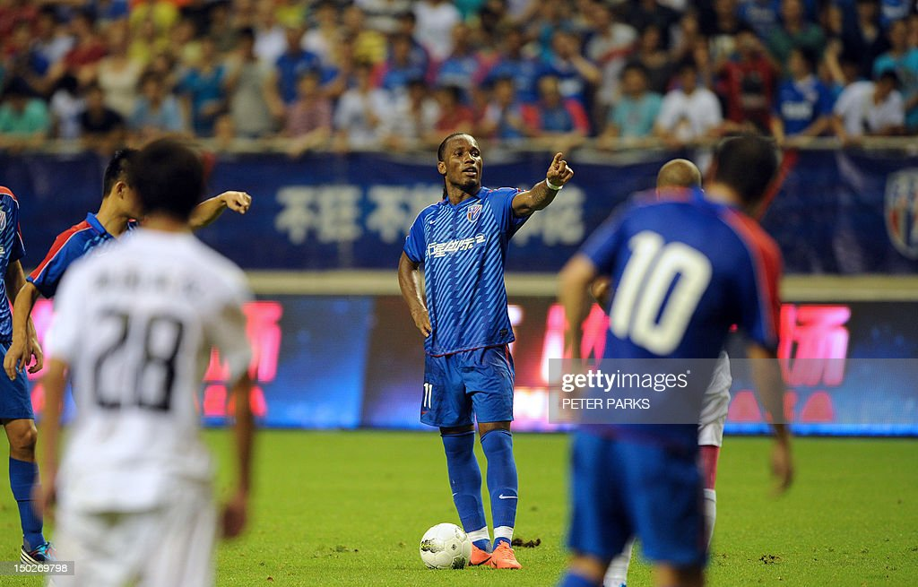 Fbl-Asia-CHN-Drogba,FOCUS by Cameron Wilson This photo taken on August 4, 2012 shows Didier Drogba (C) gesturing as he plays for Shanghai Shenhua FC in their game against Hangzhou Greentown in Shanghai Hongkou Stadium. A month after arriving in China, Drogba is living up to the expectations of fans and players who have given him the new nickname 'Devil Beast' for his strength. AFP PHOTO/Peter PARKS
