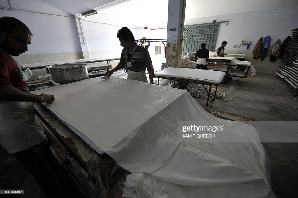Fbl-WC2010-PAK-Asia-balls FEATURE by Shahid Hashmi In this picture taken on February 23, 2010, Pakistani workers laminate a sheet of leather before it is made into footballs at a factory in Sialkot. Outrage in the West over child labour and the onset of machine-made balls -- mean that the five million balls suppliers are readying for South Africa will be for training and promotional uses only. Sialkot gained international celebrity status when it produced the 'Tango' ball for the 1982 World Cup in Spain, kicking off a lucrative industry and Pakistan's foreign exchequer. The town manufacturers sports equipment sold all over the world. Over the last decade, Pakistan on average exported 40 million balls worth 210 million dollars produced annually by some 60,000 highly skilled labours.