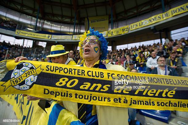 A Fc Sochaux' supporter holds a scarf reading ''Supporter of FC Sochaux Montbeliard 80 years of pride since and forever part of Sochaux'' as she...