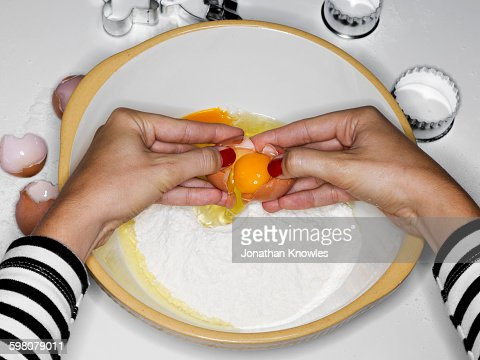 Feamle cracking egg into bowl with flour
