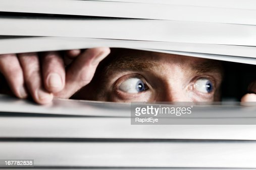 Fearful man looking sideways through venetian blind