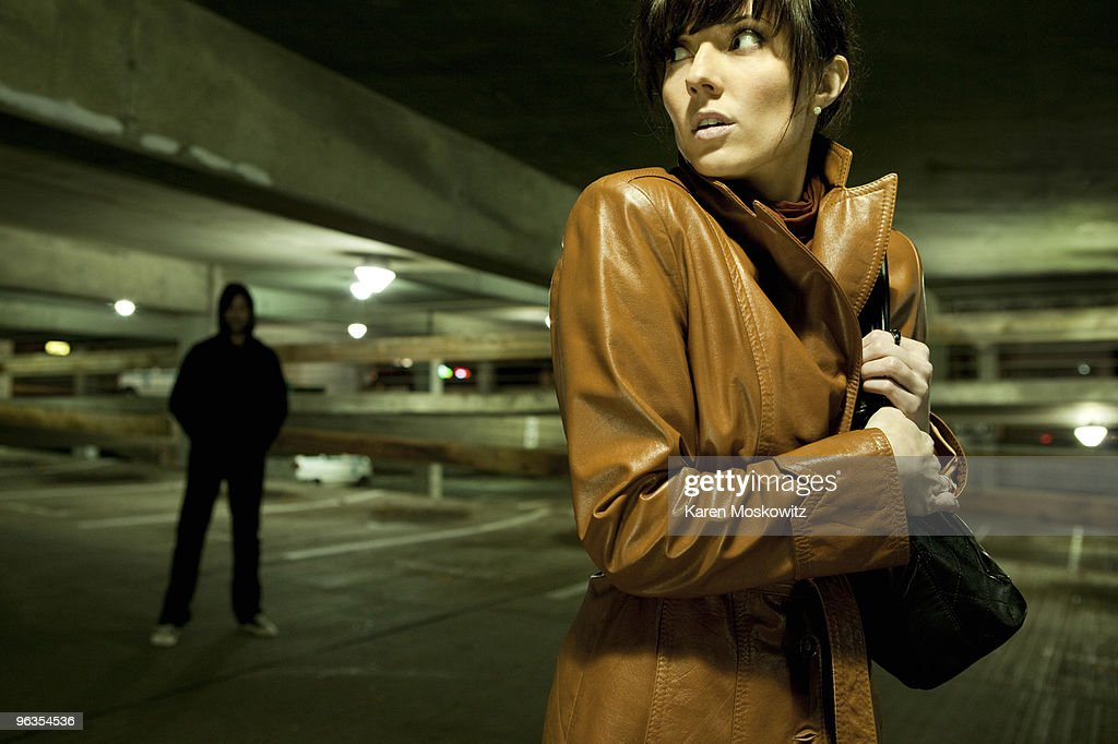 fearful woman looking over her shoulder at man : Stock Photo