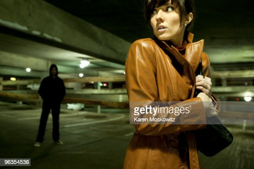 fearful woman looking over her shoulder at man : Foto de stock
