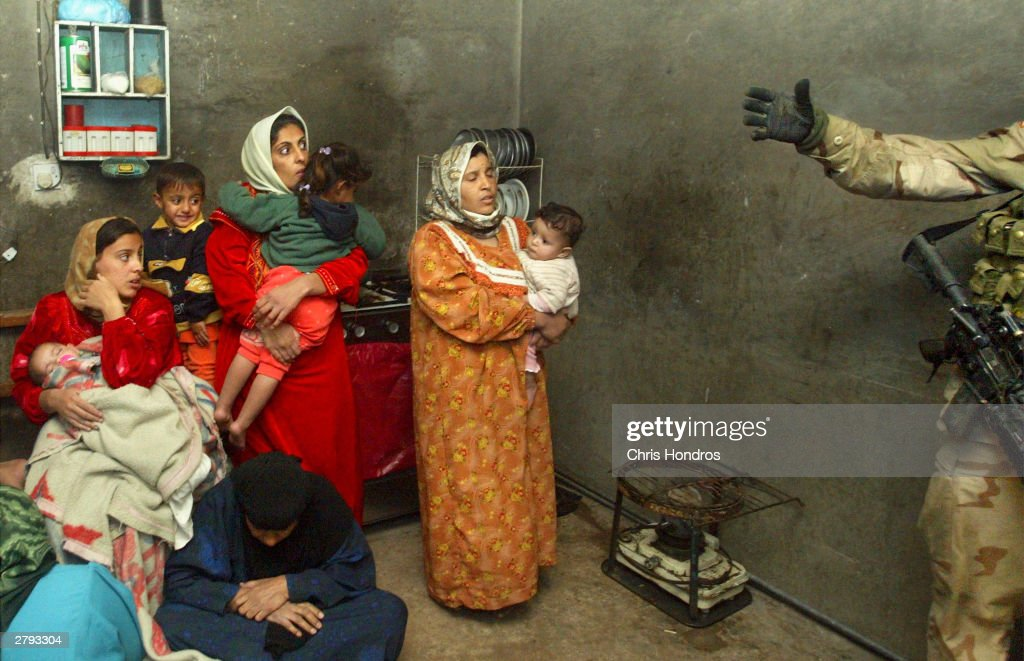 Fearful women and children watch paratroopers in the 1-504th regiment of the 82nd Airborne Division, nicknamed the 'Red Devils' raid their house, a suspected militant compound on November 26, 2003 at in Nassar el al Salaam, Iraq. The overnight raid netted two men suspected of militant activities against American forces.
