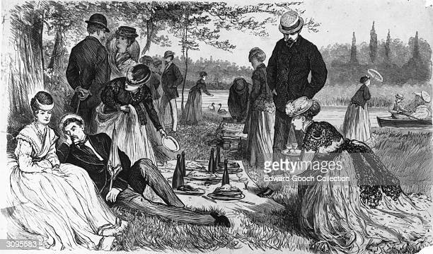 A feast is spread out on the grass by a group of ladies and gentlemen picnicking on the banks of a river