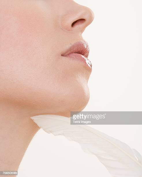 Feather touching woman's chin