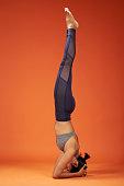 Feathered peacock yoga pose. Woman handstand in yoga asana on orange studio background