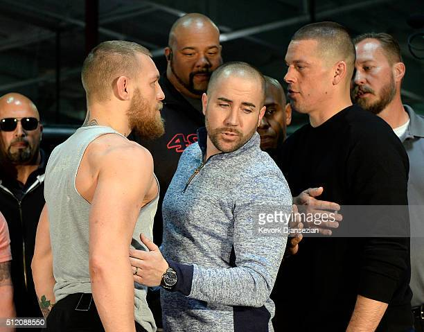 UFC featherweight champion Conor McGregor and lightweight contender Nate Diaz are held apart by Dave Sholler UFC vice president of public relations...