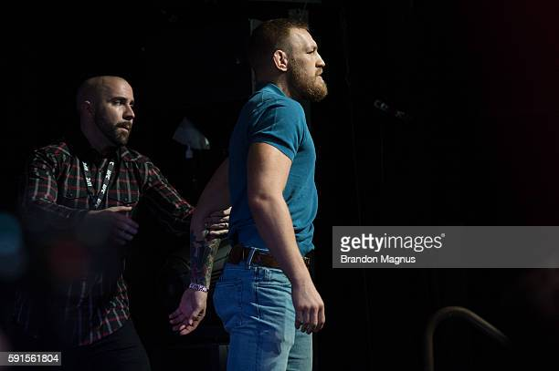 UFC featherweight champion Conor McGregor is held back by the UFC VP of Public Relations Dave Sholler during the UFC 202 Press Conference at David...