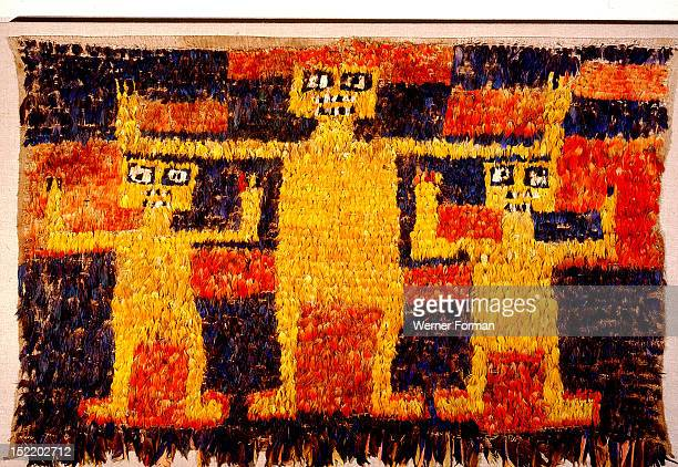 A featherwork tabard from the Nazca/Huari transitional period The design of three standing figures with raised arms is worked in red blue and yellow...