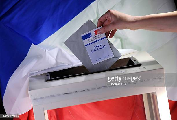 A feature picture taken on April 17 2012 in Paris shows a person casting his vote with a French electoral card in ballot box with a French national...