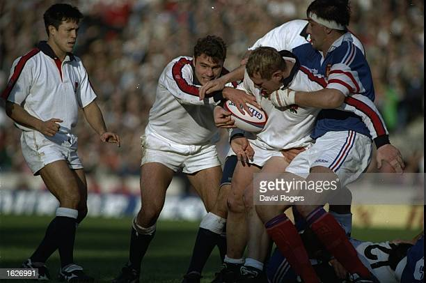 Tony Underwood stands watching as Olivier Roumat of France tries to get the ball away from Dean Richards of England and Ben Clarke in the England v...