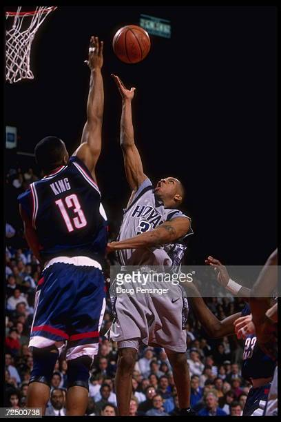 Guard Allen Iverson of the Georgetown Hoyas tries to lift the ball above the long arm of forward Kirk King of the Connecticut Huskies in this Big...