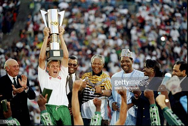Neil Touey of South Africa lifts the African nations Cup with Nelson Mandela on his right hand side after the African Nations Cup final match against...