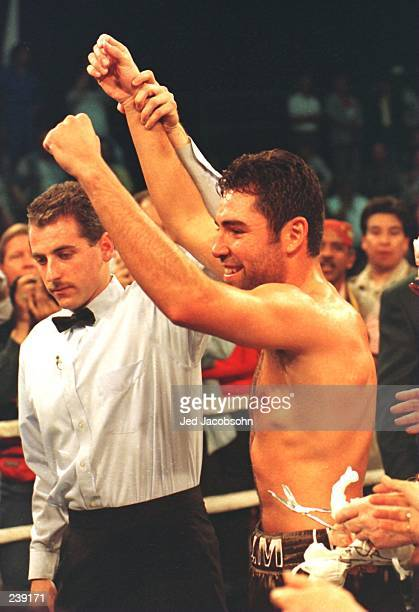 Oscar De La Hoya celebrates as referee Mitch Halpern raises his hands in victory following his second round technical knock out of Darryl Tyson at...