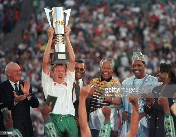 The captain of the winners of the African Cup of Nations Final Neil Tovey of South Africa holds the cup aloft after President Mandela presented it to...