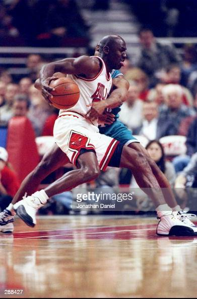Guard Michael Jordan of the Chicago Bulls moves the ball during a game against the Charlotte Hornets at the United Center in Chicago Illinois The...