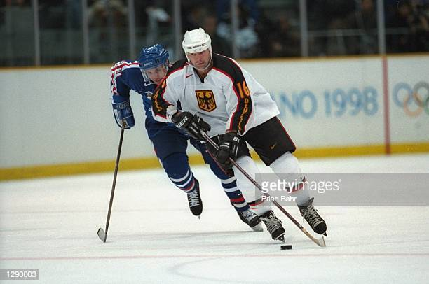 Benoit Doucet of Germany being pursued by Jan Pardavy of Slovakia during the mens preliminary round of the Ice Hockey at the Big Hat stadium in the...