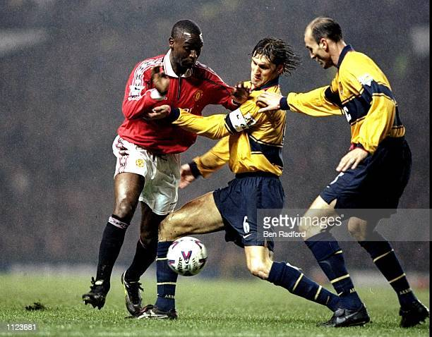Andy Cole of Manchester United faces Tony Adams and Steve Bould of Arsenal in the FA Carling Premiership match at Old Trafford in Manchester England...